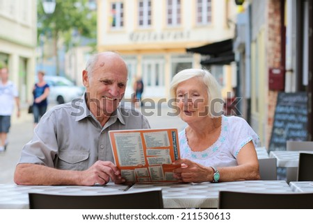 Happy active senior couple enjoying time together in outdoors street cafe on a summer day in typical European town - active retirement concept - stock photo