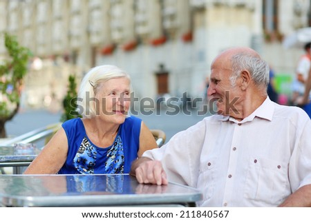 Happy active senior couple enjoying time together waiting for their order in outdoors street cafe on a summer day in typical European town - active retirement concept - stock photo