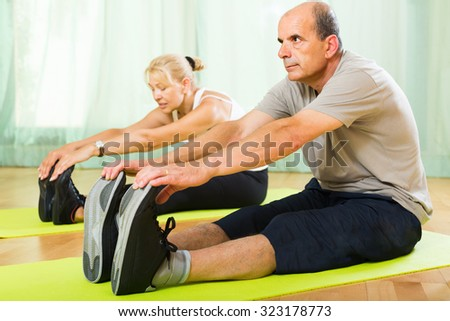 Happy active senior mature spouses warming up muscles before exercising at home - stock photo