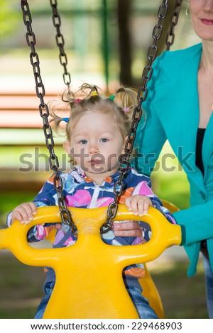 Happy adorable child girl on swing on playground near kindergarten Montessori on summer day - stock photo