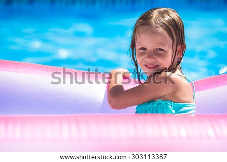Happy adorable girl having fun in outdoor swimming pool - stock photo