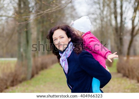 Happy adorable kid boy sitting on his mom's shoulders and laughing. Pretty Mother and Little Girl Having Fun Together. Beautiful mother carry little girl on shoulders - stock photo