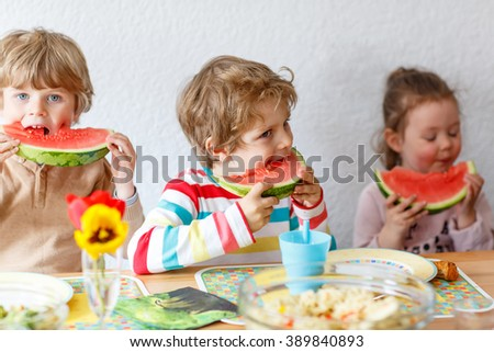 Happy adorable kid boys and little girl eating healthy food, fresh watermelon in kindergarten, nursery or at home. Fresh fruits as organic bio snack for children. Three kids. - stock photo