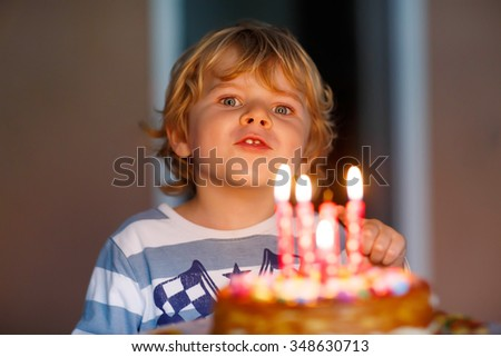 Happy adorable kid celebrating his birthday and blowing candles on homemade baked cake, indoor. Birthday party for kids. Focus on child - stock photo