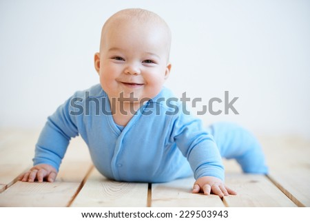 Happy adorable little baby boy with a beaming smile raising himself up on his hands as he crawls on the floor to look at the camera - stock photo