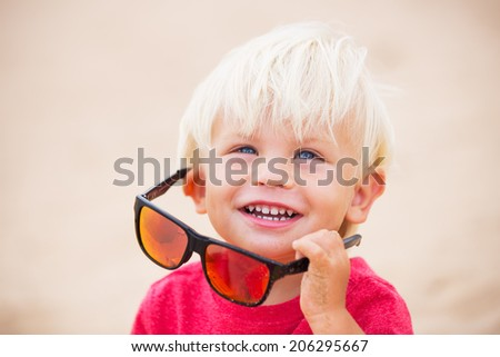 Happy adorable little boy at the beach in red sun glasses - stock photo