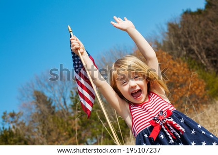 Happy adorable little girl smiling and waving American flag outside - stock photo