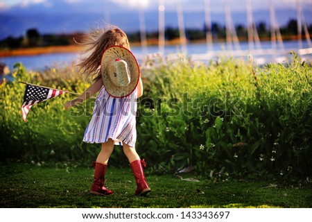 Happy adorable little girl smiling and waving American flag outside, her dress with strip and stars, cowboy hat. Smiling child celebrating 4th july - Independence Day - stock photo