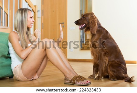 Happy adult girl sitting on floor with red Irish setter  - stock photo