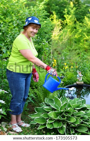 Happy adult woman gardener watering the plants that grows near the garden pond - stock photo