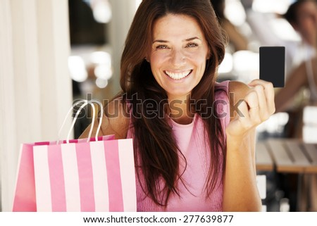 Happy adult woman with credit card and shopping bag - stock photo