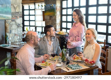 Happy adults eating out in a fashionable restaurant while young and beautiful waitress is serving them - stock photo