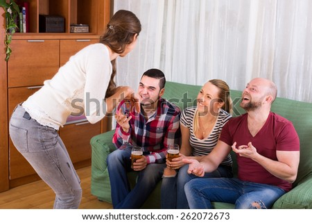 Happy adults playing charades indoor and laughing - stock photo