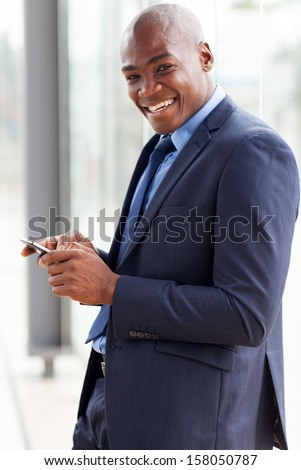 happy african american businessman reading email on smart phone - stock photo
