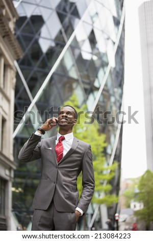 Happy African American businessman using cell phone outside building - stock photo