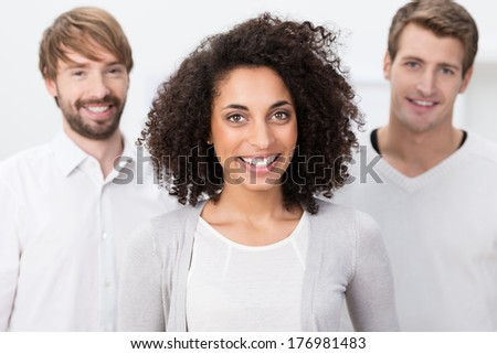 Happy African American businesswoman posing with two handsome male colleagues as they group together to smile at the camera - stock photo