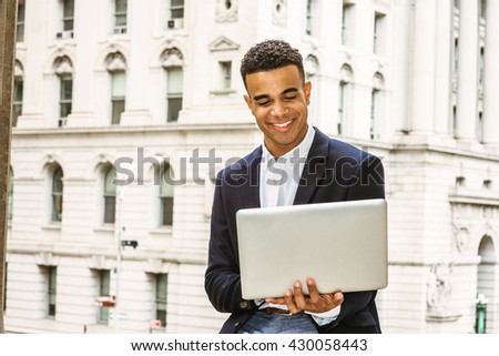 Happy African American college student studying in New York, wearing black blazer, sitting by vintage office building on campus, reading, working on laptop computer, smiling. Instagram filtered effect - stock photo