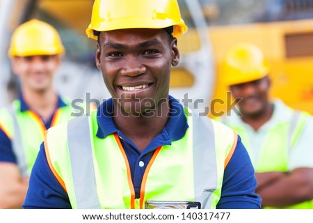 happy african american construction worker in front of colleagues - stock photo
