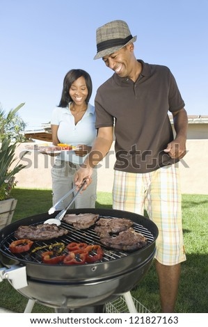 Happy African American couple cooking together in lawn - stock photo