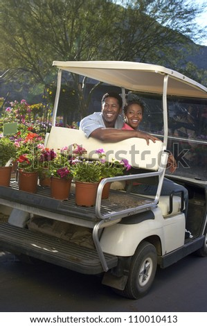 Happy African American couple in golf cart at botanical garden - stock photo