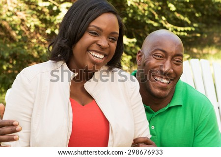 Happy African American couple outdoors looking away - stock photo