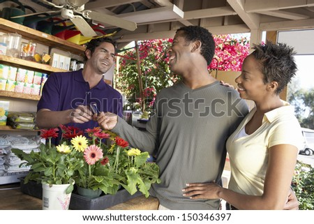 Happy African American couple paying for plants in nursery - stock photo
