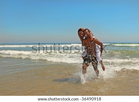 Happy African American Couple Splashing in the Ocean at the Beach - stock photo