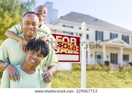 Happy African American Family In Front of Sold For Sale Real Estate Sign and House. - stock photo