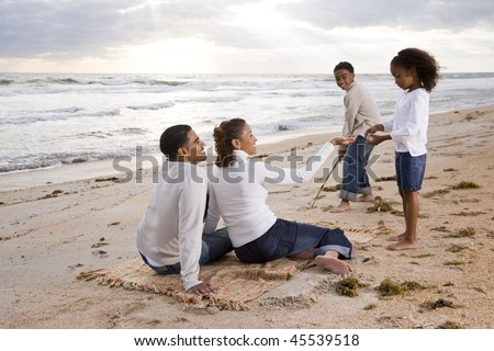 Happy African-American family of four standing on beach with beautiful sunlight - stock photo