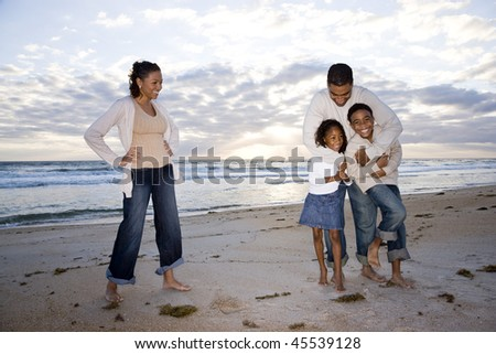 Happy African-American family with two children hugging on beach - stock photo