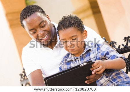 Happy African American Father and Mixed Race Son Having Fun Using Touch Pad Computer Tablet Outside. - stock photo
