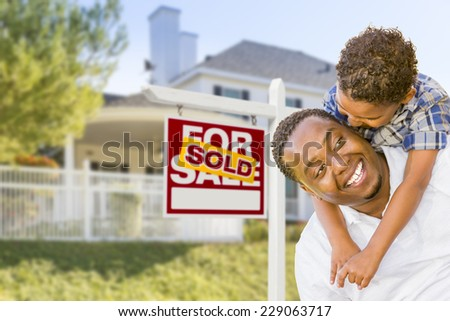 Happy African American Father and Mixed Race Son In Front of Sold Home For Sale Real Estate Sign and New House. - stock photo