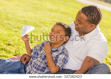 Happy African American Father and Mixed Race Son Playing with Paper Airplanes in the Park. - stock photo