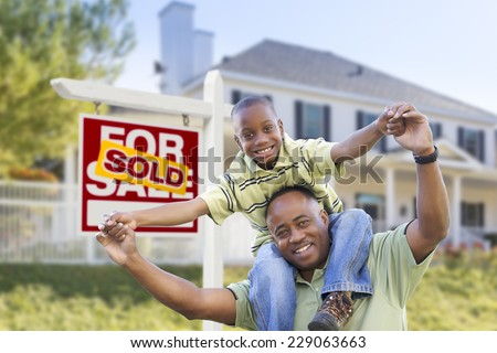 Happy African American Father and Son in Front of Home and Sold For Sale Real Estate Sign. - stock photo