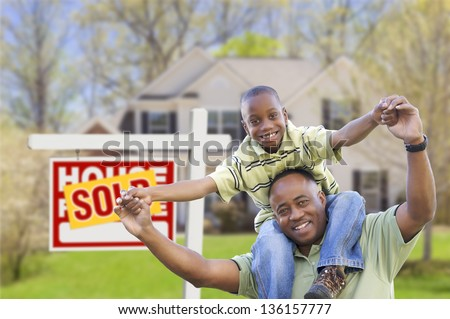 Happy African American Father and Son in Front of New Home and Sold Real Estate Sign. - stock photo