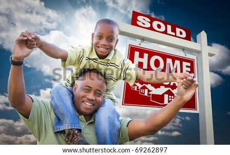 Happy African American Father with Son In Front of Sold Home For Sale Real Estate Sign and Sky. - stock photo