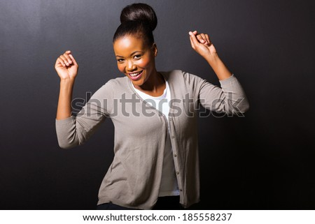 happy african american girl dancing on black background - stock photo
