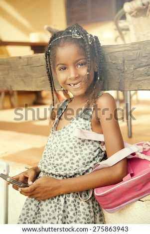 Happy african american girl smiling with backpack and mobile phone - stock photo