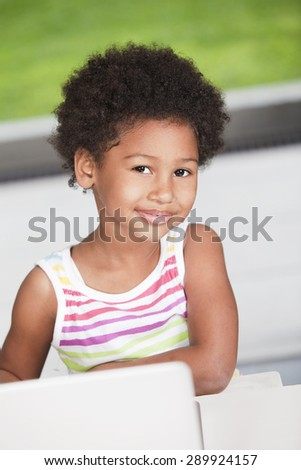 Happy african american girl with computer - stock photo