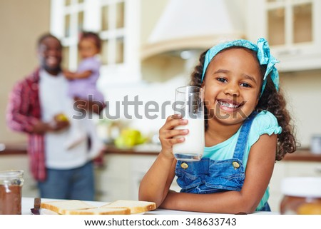 Happy African-American girl with glass of milk looking at camera on background of her father and sister - stock photo