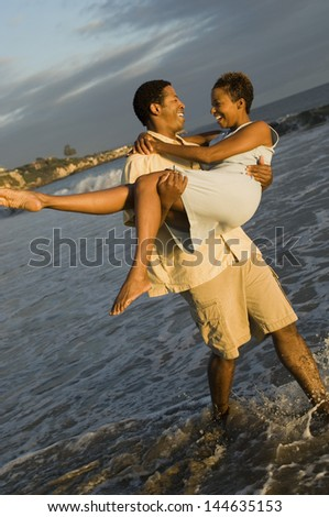 Happy African American man carrying cheerful woman in the ocean - stock photo
