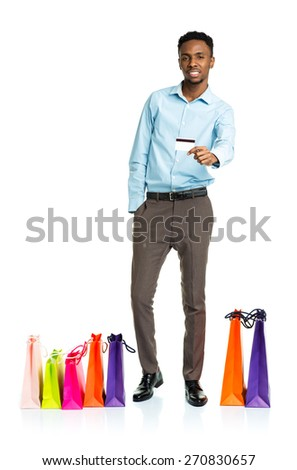 Happy african american man with shopping bags and holding credit card on white background. Holidays concept - stock photo