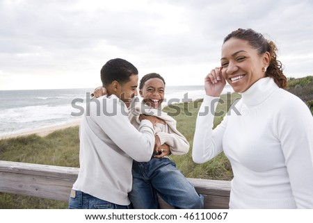 Happy African-American parents with ten year old boy laughing at beach - stock photo