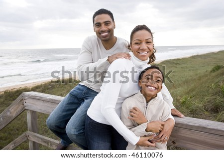 Happy African-American parents with ten year old boy smiling and hugging at beach - stock photo