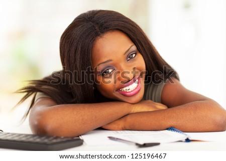 happy african american university student lying on desk - stock photo