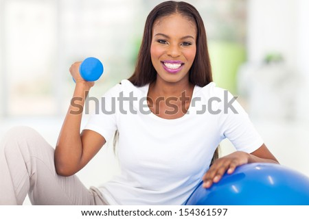 happy african american woman doing fitness exercise at home - stock photo