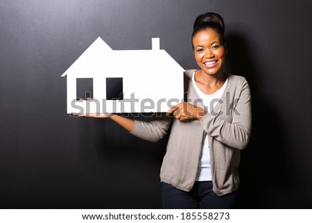 happy african american woman showing house symbol over black background - stock photo