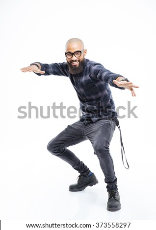 Happy african american young bearded man in glasses balancing and dancing  - stock photo