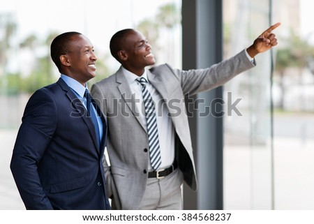 happy african business men pointing in modern office - stock photo