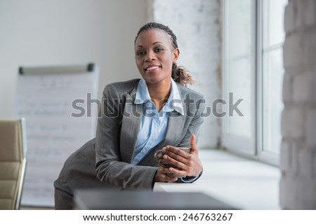 Happy african business woman enjoying the coffee break at her office and looking at window - stock photo